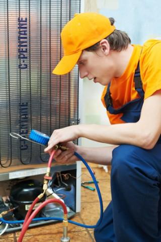 Eine Kälte-Mechatroniker repariert einen Kühlschrank.